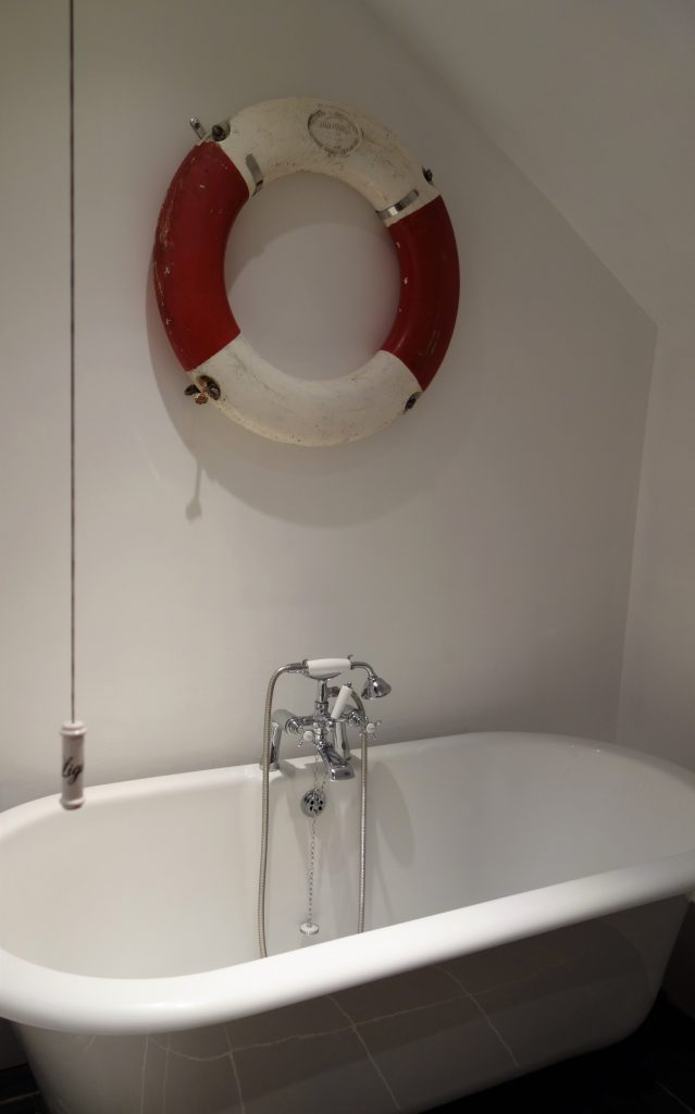 A white roll top bathtub with a red and white lifebelt on the wall above.