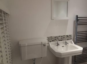 White porcelain WC and sink in bright white painted bathroom